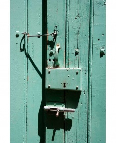 Green painted door with eclectic security measures